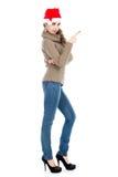 毛线衣的指向手指的少妇和牛仔裤支持 库存照片