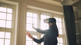 毛线衣的笑的少女获得乐趣用站立虚拟现实玻璃移动的手在轻的演播室与 影视素材