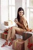 毛线衣的美丽的女孩坐窗口 礼物,新年 库存照片