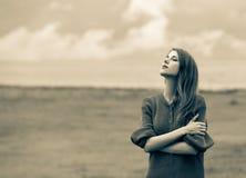 毛线衣的美丽的成人女孩在麦田 库存照片