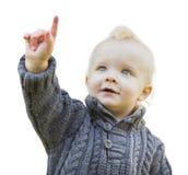 毛线衣的逗人喜爱的小男孩指向在白色的 免版税图库摄影
