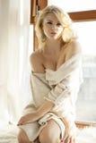 毛线衣的年轻亭亭玉立的性感的妇女在窗口 库存图片