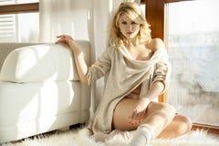 毛线衣的年轻亭亭玉立的性感的妇女在窗口 免版税库存照片
