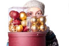 毛线衣的年轻逗人喜爱的微笑的女孩,拿着一个箱子圣诞节装饰 冬天, Cristmastime,新年假日 免版税库存照片