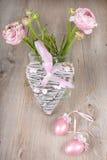 毛茛属在有桃红色心脏的一个花瓶开花 免版税库存照片