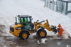 毛虫与犁雪的除雪机的轮子装载者在飞雪期间 免版税图库摄影