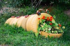毛虫的花圃雕塑由老汽车轮胎制成 免版税库存图片