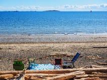 毯子和椅子在海滩 免版税库存图片