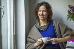 毯子的年轻愉快的妇女在与一杯茶的窗口附近 免版税图库摄影