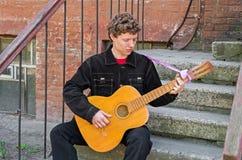 从贫民窟的吉他弹奏者 库存图片