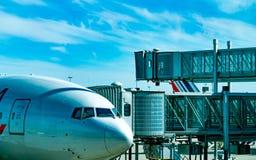 民航停放在乘客的喷气机桥梁在机场离开 飞机乘客搭乘桥梁靠码头与蓝色 库存图片