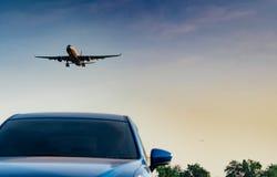 民航 客机接进着陆蓝色SUV汽车在有天空蔚蓝和云彩的机场在日落 到来飞行 库存照片