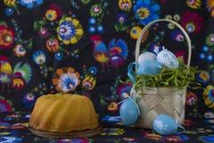 民间样式复活节装饰用在被绘的纺织品背景的白色和蓝色鸡蛋 库存照片
