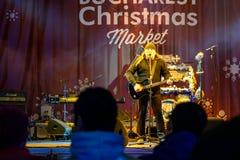 民间音乐家Vasile唱歌在圣诞节市场上的Seicaru任意共同安排街市布加勒斯特 免版税库存照片