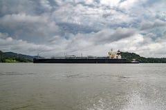 气体在巴拿马运河的运输船 带来雨的黑暗的云彩 免版税库存图片