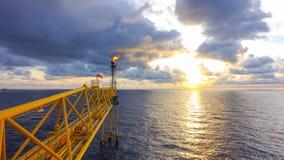 从气体近海处生产平台的火光桥梁与sunri 免版税库存图片