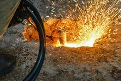气割在工业生产和冶金学,工作者方面切开与气体火炬和氧气的金属 免版税库存图片