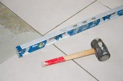气泡水准和橡胶短槌在地板盖瓦 图库摄影
