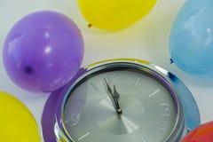气球和到达12个o时钟午夜的钟针 免版税图库摄影