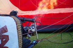 气球飞行员烧热空气并且膨胀他的气球为做准备离开 库存照片