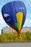 气球驾驶者攀登气球入在秋天晴朗的下午的天空在一个小镇的房子旁边 垂直的框架 库存照片