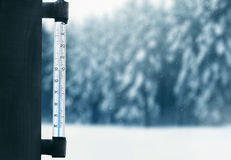 气象学、预测和冬天风化季节概念-在一个玻璃窗的温度计有多雪的冬天森林背景 免版税图库摄影