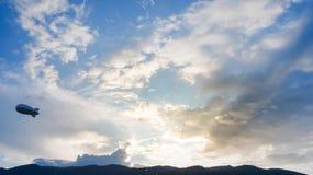 氦气软式小型飞艇广告轻快优雅浮动日落天空和山 免版税库存照片