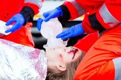 给氧气的救护车医生女性受害者 免版税库存照片