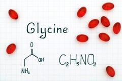 氨基乙酸化学式与红色药片的 库存照片