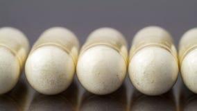 氨基葡萄糖胶囊,食物在光滑的黑暗的背景,宏观图象的补充药片 免版税图库摄影