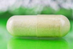 氨基葡萄糖胶囊,食物在光滑的绿色背景,宏观图象,软性的补充药片弄脏了bokeh圈子 免版税图库摄影