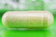 氨基葡萄糖胶囊,食物在光滑的绿色背景,宏观图象,软性的补充药片弄脏了bokeh圈子 免版税库存图片