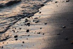 水一个接近的看法在湖岸的在日落,与沙子和小的圆的石头细节  库存图片