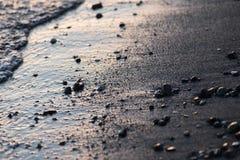 水一个接近的看法在湖岸的在日落,与沙子和小的圆的石头细节  免版税库存图片