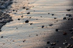 水一个接近的看法在湖岸的在日落,与沙子和小的圆的石头细节  免版税库存照片