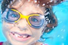 水下儿童滑稽的女孩的风镜 免版税库存照片