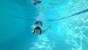 水下漂浮,妇女下潜到水里在蓝色水池游泳与开放眼睛并且微笑 股票视频