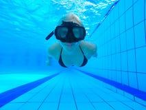 水下的图片:与面具和蓝色比基尼泳装的妇女游泳在游泳池 免版税库存图片
