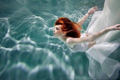水下的女孩 一件白色礼服的美丽的红发妇女,游泳在水下 免版税库存图片