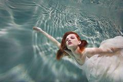 水下的女孩 一件白色礼服的美丽的红发妇女,游泳在水下 免版税图库摄影