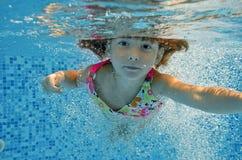 水下的子项跳到游泳池 免版税库存图片