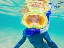 水下的自然课,潜航在清楚的蓝色海的男孩 免版税库存照片