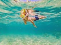 水下的自然课,潜航在清楚的蓝色海的男孩 免版税图库摄影
