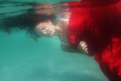 水下红色的礼服的新美丽的妇女 免版税库存图片