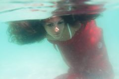 水下红色的礼服的新美丽的妇女 库存照片