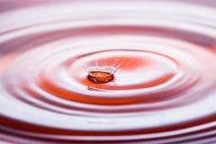 水下落在橙色口气的飞溅冠 库存图片