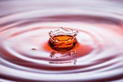 水下落在橙色口气的飞溅冠 免版税图库摄影