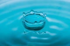 水下落在蓝色口气的飞溅冠 免版税库存图片