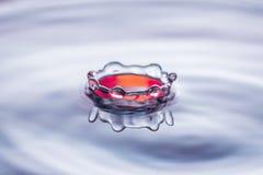 水下落在蓝色和红色口气的飞溅冠 免版税图库摄影