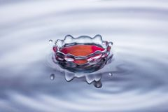 水下落在蓝色和红色口气的飞溅冠 免版税库存图片